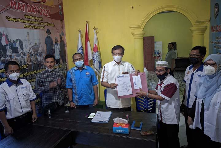 Ketua KSPI Lampung Sulaiman Ibrahim menyerahkan tuntutan buruh Lampung dan diterima Kadisnaker Agus Nompitu.