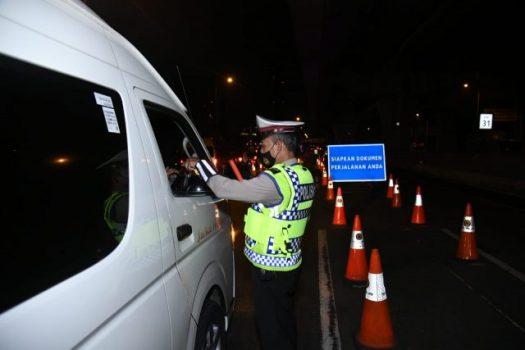 Petugas polisi dari Polda Metro Jaya memeriksa surat-surat pengendara pada masa larangan mudik Idul Fitri 2021.