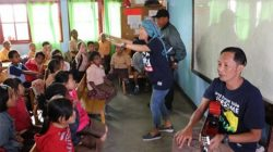 Ivan Sumantri Bonang (duduk memegang gitar) dan Iin Mutmainah sedang mendongeng di sebuah ruang kelas Sekolah Dasar.