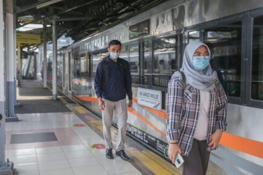 Calon penumpang KA berjalan memasuki kereta dengan mengenakan APD yang telah disyaratkan