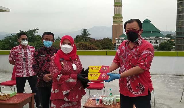 Sekretaris PSMTI Lampung Steven Chow menyerahkan bantuan secara simbolis dan diterima Walikota Bandarlampung Eva Dwiana.
