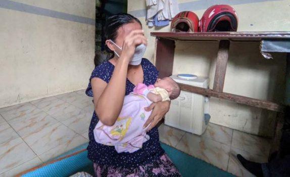 Sari menangis sambil menggendong bayinya yang tidak memiliki anus.