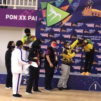 Meiyusi Ade Putra menerima medali emas setelah menjuari lomba senam nomor palang sejajar pada PON XX Papua, Senin sore waktu Papua (4/10/2021). Foto: Don Pechy